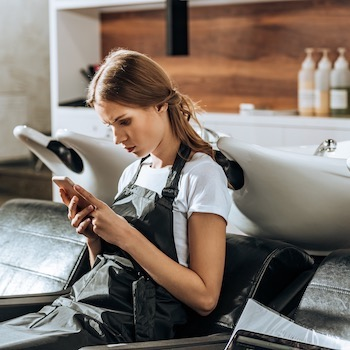 beautiful young hairdresser using smartphone in beauty salon