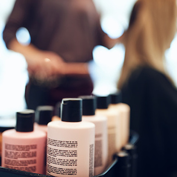 Closeup of shampoo and conditioner bottles on a tray in a hair salon with a hairdresser styling a client's hair in the background